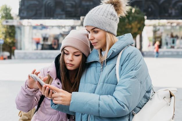 Przyjaciele patrząc na telefon na zewnątrz w zimie