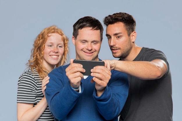 Przyjaciele patrząc razem na swoje zdjęcia przez telefon