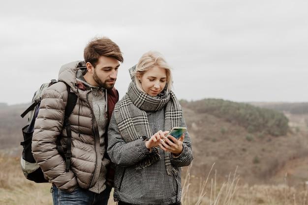 Przyjaciele patrzeje telefon outdoors