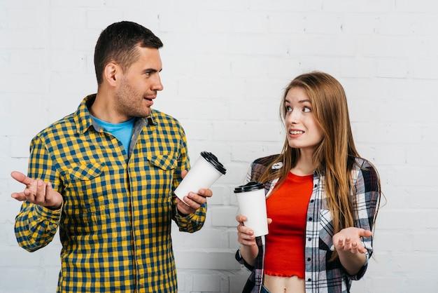 Przyjaciele patrzeje zmieszany podczas gdy trzymający filiżankę kawy