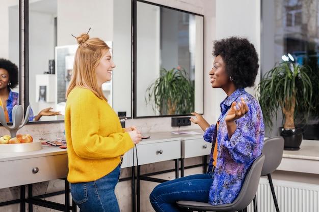 Przyjaciele. piękna ciemnoskóra kobieta z kręconymi włosami rozmawiająca z uśmiechniętą przyjaciółką siedząc na krześle