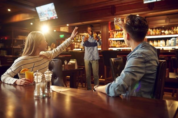 Przyjaciele piją alkohol i bawią się przy stoliku w barze. grupa ludzi odpoczywa w pubie, nocnym stylu życia, przyjaźni, uroczystościach