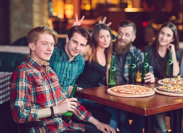 Przyjaciele piją drinki w barze, siedzą przy drewnianym stole z piwem i pizzą.