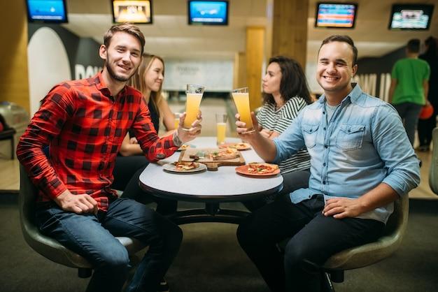 Przyjaciele piją i jedzą pizzę w kręgielni