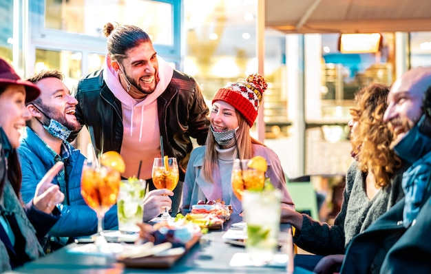Przyjaciele piją koktajle w restauracji z barem na zewnątrz