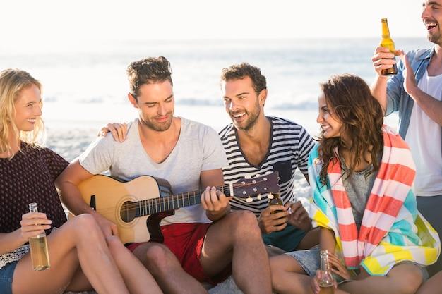 Przyjaciele piją piwo i grają na gitarze