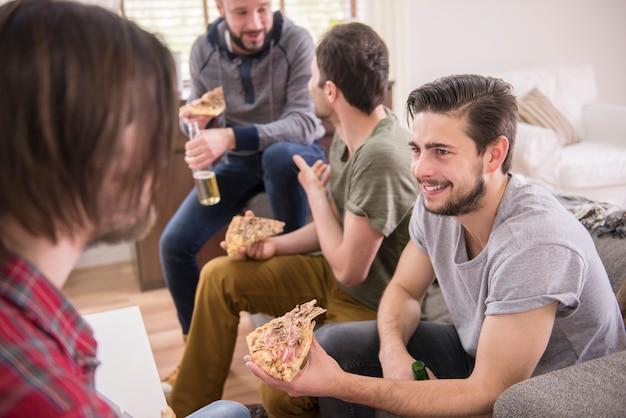 Przyjaciele piją piwo i jedzą pizzę