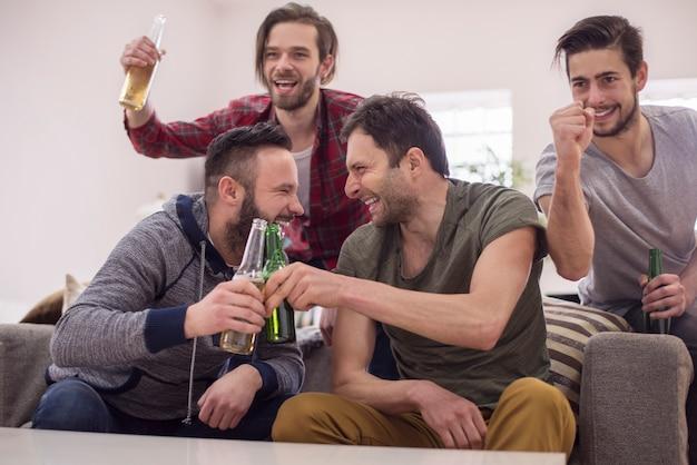 Przyjaciele piją piwo i oglądają mecz piłki nożnej