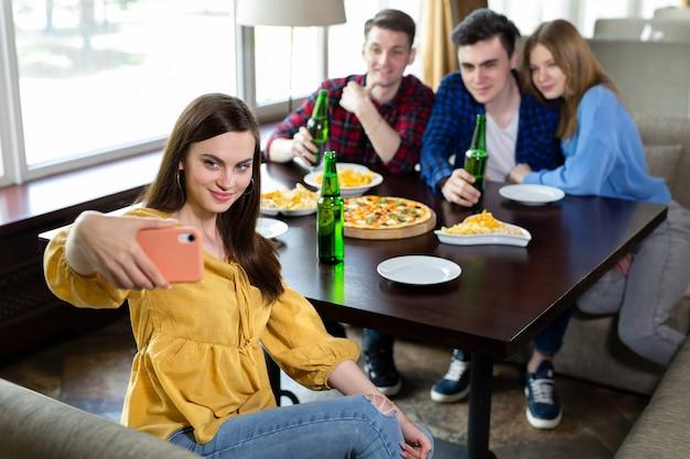 Przyjaciele piją piwo, jedzą pizzę, rozmawiają i śmieją się i robią selfie w aparacie smartfona