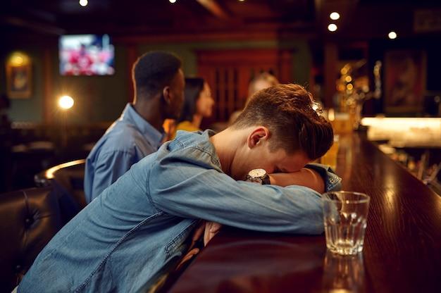 Przyjaciele piją piwo, mężczyzna śpi przy ladzie w barze. grupa ludzi wypoczywa w pubie, nocny tryb życia, przyjaźń