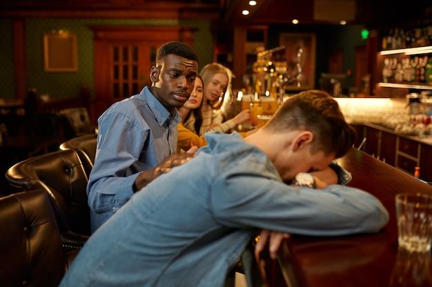 Przyjaciele piją piwo, mężczyzna śpi przy ladzie w barze
