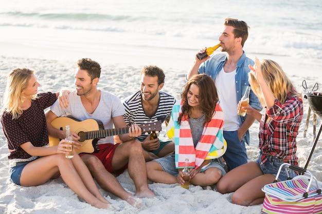 Przyjaciele piją piwo na plaży