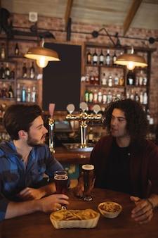 Przyjaciele piją piwo w pubie