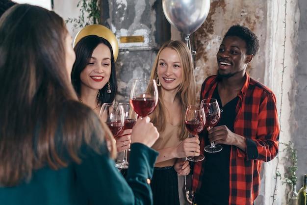 Przyjaciele piją tosty z winem podczas świętowania w restauracji?