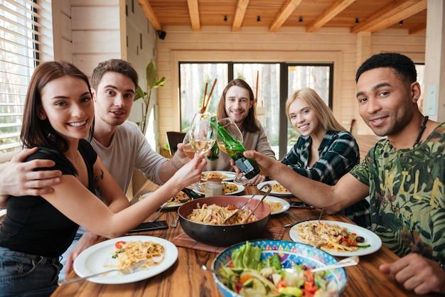 Przyjaciele piją wino i szczęk szkła w kuchni