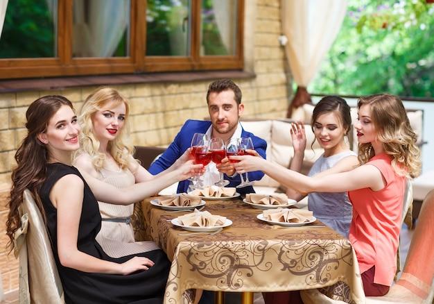 Przyjaciele piją wino na letnim tarasie.