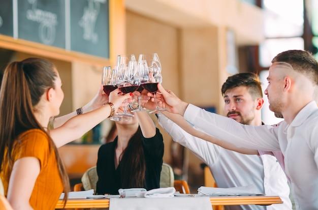 Przyjaciele piją wino na tarasie restauracji.