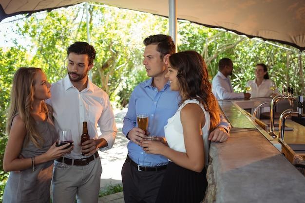 Przyjaciele pijący alkohol przy ladzie