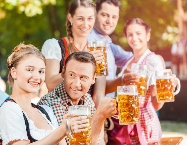 Przyjaciele pijący piwo jonowe oktoberfest
