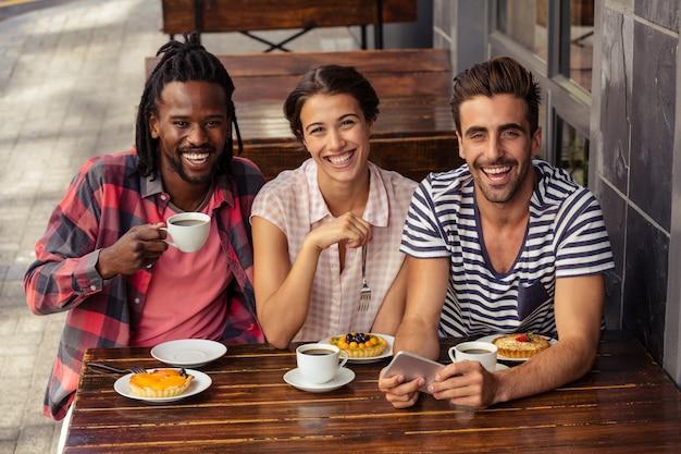 Przyjaciele pije kawę i używa smartphone