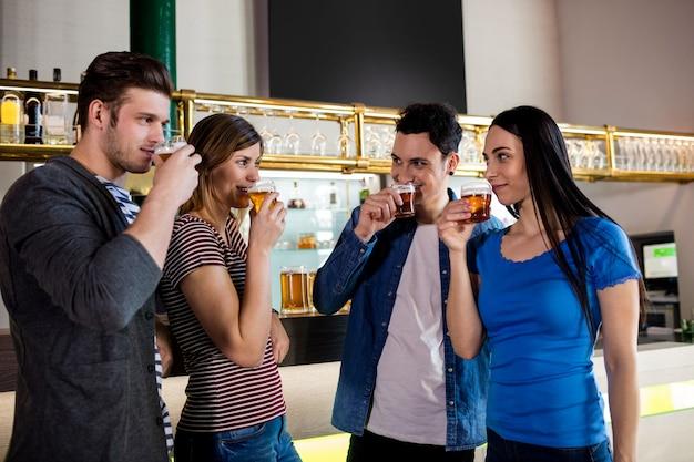 Przyjaciele pije piwo przy barze