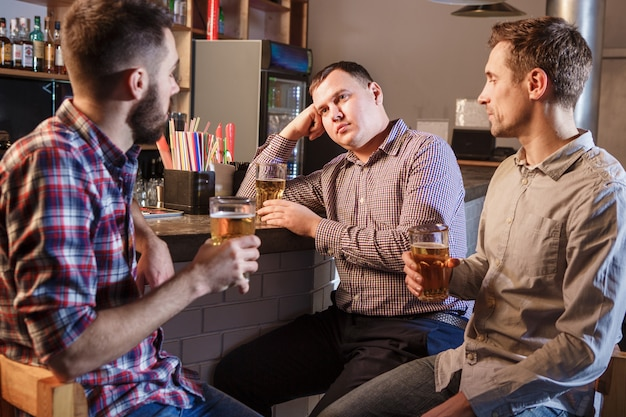 Przyjaciele pije piwo w kasie w pubie