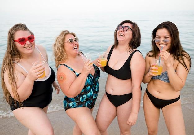 Przyjaciele pije sok przy plażowym frontowym widokiem