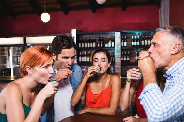 Przyjaciele pije tequili przy stole