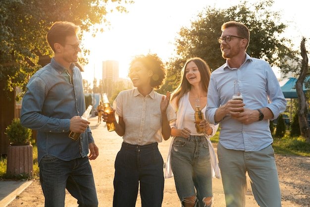 Przyjaciele płci męskiej i żeńskiej spędzają razem czas na świeżym powietrzu i piją piwo