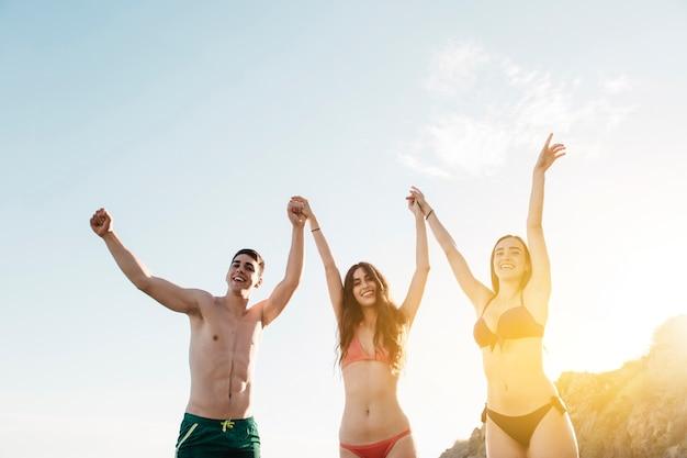 Przyjaciele podnosi ręki przy plażą