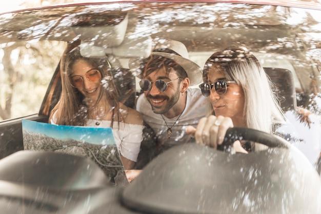 Przyjaciele podróżuje w samochodzie patrząc na mapę