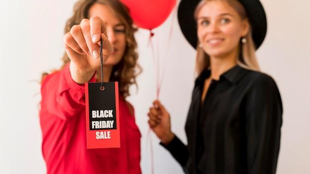 Przyjaciele pokazujący czarną etykietę piątek