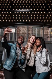 Przyjaciele pozuje dla selfie środka strzału