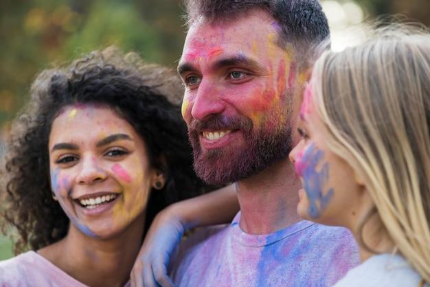 Przyjaciele pozuje z malować twarzami przy festiwalem