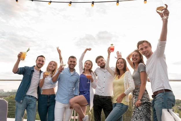 Przyjaciele pozuje z napojami na przyjęciu