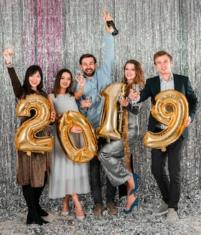 Przyjaciele pozuje z złotym balonu nowego roku przyjęciem