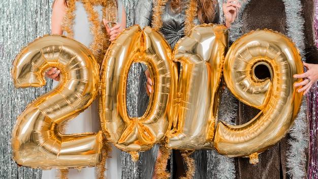 Przyjaciele pozuje z złotymi balonami przy nowego roku przyjęciem