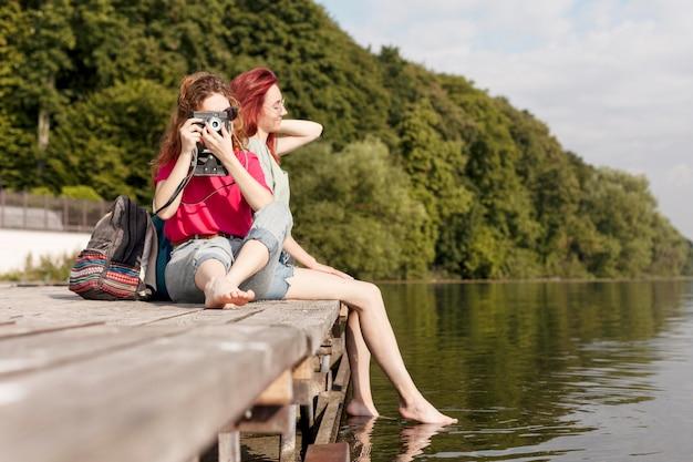Przyjaciele przebywający na doku i robiąc zdjęcia