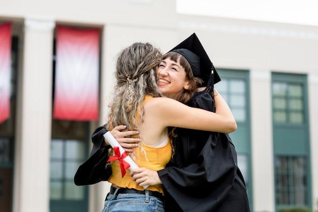 Przyjaciele przytulają się na ceremonii ukończenia szkoły