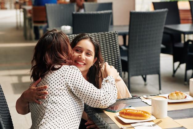 Przyjaciele przytulający się przy stoliku w kawiarni