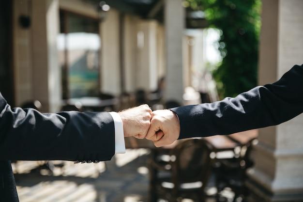 Przyjaciele pukają ręce podczas ceremonii ślubnej