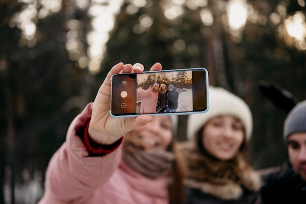 Przyjaciele razem biorąc selfie na zewnątrz w zimie