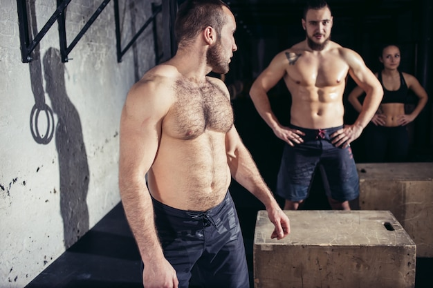 Przyjaciele relaksujący i odpoczywający po treningu w siłowni przekrojowej