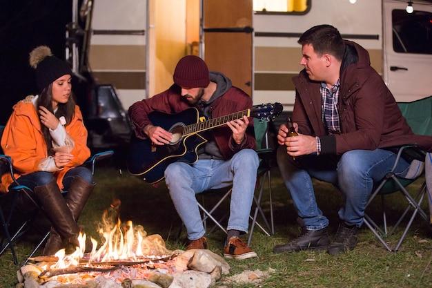 Przyjaciele relaksujący się i grający na gitarze przy ognisku z retro kamperem w tle. żarówki.