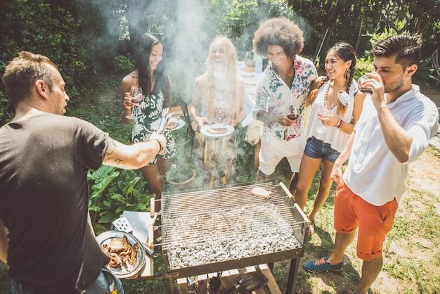 Przyjaciele robi grillowi w ogródzie