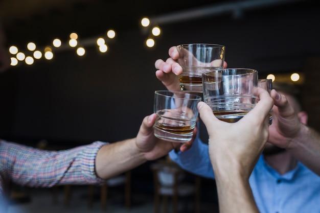Przyjaciele robią okrzyki z szklankami whisky