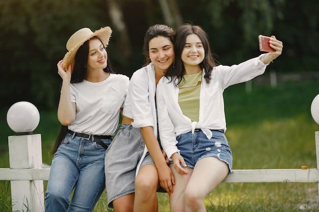 Przyjaciele robią selfie. dziewczyna w kapeluszu. kobieta w białej koszulce.