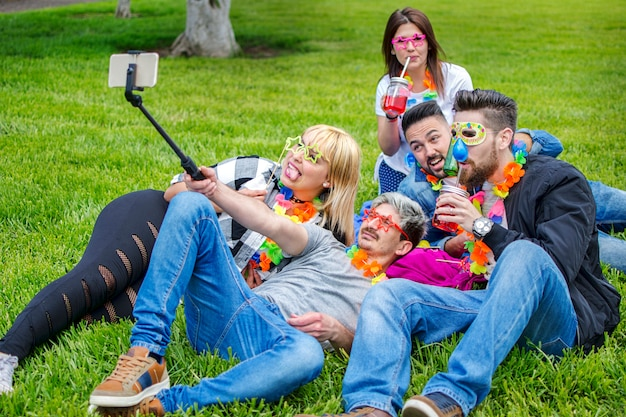 Przyjaciele robią selfie na letnim festiwalu z maskami i naszyjnikami