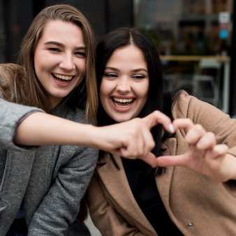 Przyjaciele robią serce palcami