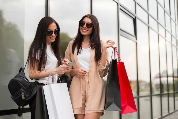 Przyjaciele robią wspólne zakupy i używają telefonu komórkowego